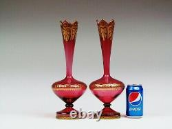 A pair of late 19th century Bohemian cranberry glass vases decorated with gilded